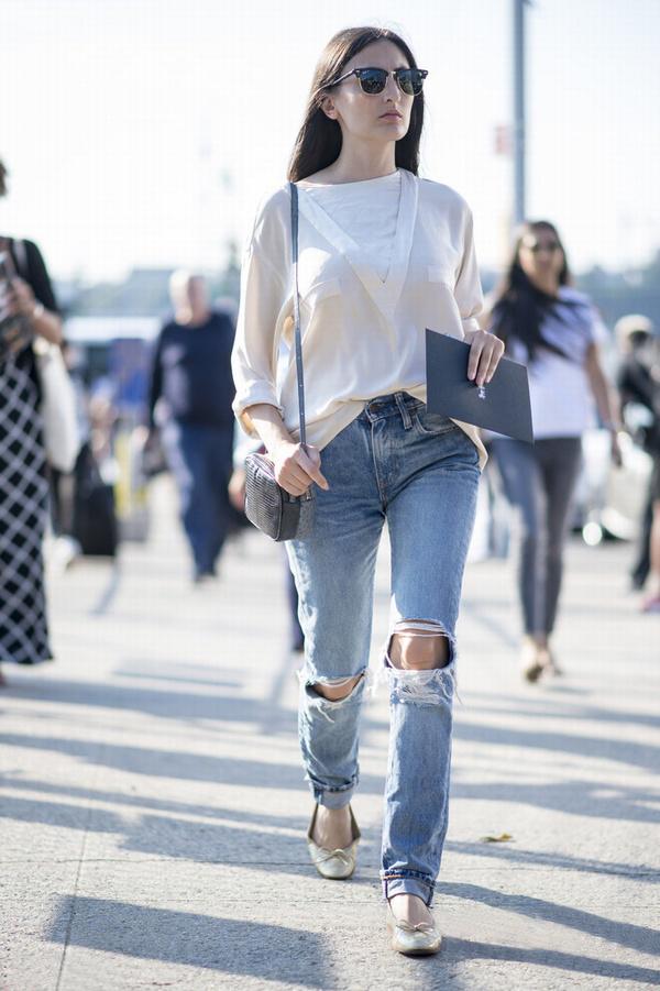 """白色上衣搭配""""摔一跤""""牛仔裤和金色船鞋简单有型,灰色迷你包更显高级质感。"""