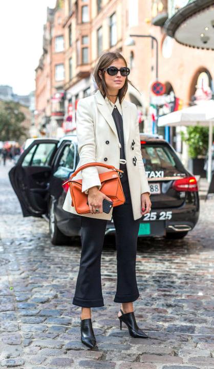 白西服+黑色九分喇叭裤+黑色尖头鞋演绎简单有型的都市OL范,桔红色几何拼接的包包很有现代摩登感。