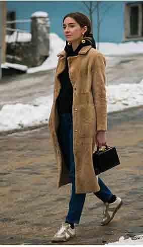 卡其色大衣内搭水洗蓝牛仔裤和黑色高领毛衣,脚踩平底鞋,耳饰选择夸张的金属系二线,让整身搭配更显质感。