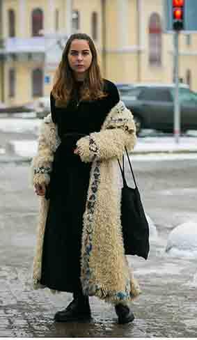 黑色丝绒连衣裙着毛毛外套,配以同色系鞋包,尽可能达到显瘦的效果。